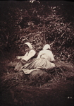 Two women resting on bundles
